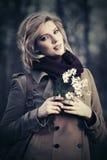 Glückliche junge Modefrau mit einem Blumengehen im Freien Lizenzfreie Stockfotos