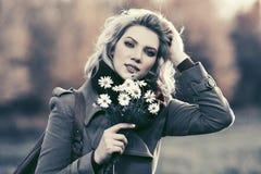 Glückliche junge Modefrau mit einem Blumengehen im Freien Lizenzfreies Stockbild