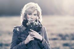 Glückliche junge Modefrau mit einem Blumengehen im Freien Lizenzfreie Stockbilder