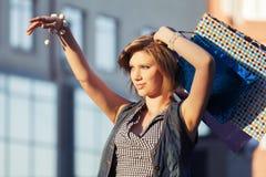 Glückliche junge Modefrau mit Einkaufstaschen auf einer Stadtstraße Lizenzfreie Stockbilder