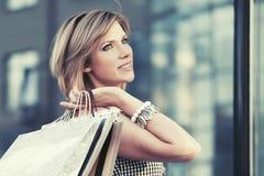 Glückliche junge Modefrau mit Einkaufstaschen gehend in das Mall Lizenzfreie Stockbilder