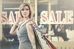 Glückliche junge Modefrau mit Einkaufstaschen gehend in das Mall Stockfotografie