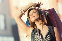 Glückliche junge Modefrau mit Einkaufstaschen gehend in Stadtstraße Lizenzfreie Stockfotos