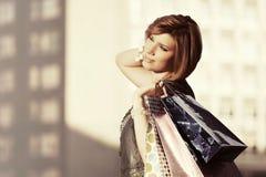 Glückliche junge Modefrau mit Einkaufstaschen gehend in Stadtstraße Lizenzfreie Stockbilder