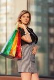 Glückliche junge Modefrau mit Einkaufstaschen im Einkaufszentrum Stockbilder