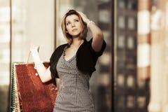 Glückliche junge Modefrau mit Einkaufstaschen im Einkaufszentrum Stockfoto