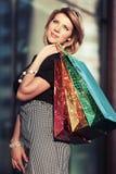 Glückliche junge Modefrau mit Einkaufstaschen im Mall Lizenzfreie Stockbilder