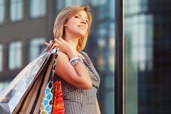 Glückliche junge Modefrau mit Einkaufstaschen im Mall Stockbild