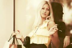 Glückliche junge Modefrau mit Einkaufstaschen im Mall Lizenzfreie Stockfotos