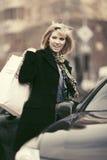 Glückliche junge Modefrau mit Einkaufstaschen nahe bei ihrem Auto Lizenzfreie Stockfotografie