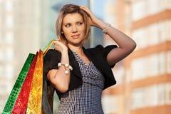 Glückliche junge Modefrau mit Fenster der Einkaufstaschen im Einkaufszentrum Lizenzfreie Stockfotos