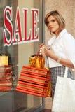 Glückliche junge Modefrau mit Fenster der Einkaufstaschen im Einkaufszentrum Lizenzfreie Stockbilder