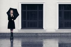 Glückliche junge Modefrau mit Regenschirm gehend in Stadtstraße lizenzfreie stockfotos