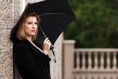 Glückliche junge Modefrau mit Regenschirm im Regen Lizenzfreie Stockbilder