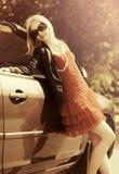 Glückliche junge Modefrau nahe bei ihrem Auto Stockfotografie