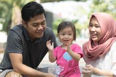 Glückliche junge moslemische Familie mit den Kindern eins, die am Park lachend am sonnigen Tag spielen lizenzfreie stockfotografie