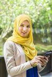 Glückliche junge moslemische Frau, die ein Telefon beim heraus schauen hält Stockfotos