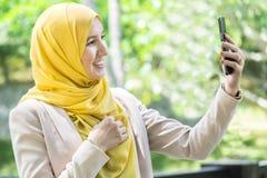 Glückliche junge moslemische Frau, die selfie nimmt Stockfoto