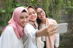 Glückliche junge Moslems der Gruppe, die zusammen selfie nehmen stockfotografie