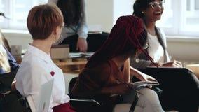 Glückliche junge multiethnische weibliche Unternehmensangestellte lachen das Hören auf Seminar bei der modernen Bürokonferenz stock video footage