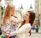 Glückliche junge Mutter, die ihre Tochter in ihren Armen in der Stadt hält Lizenzfreie Stockfotos