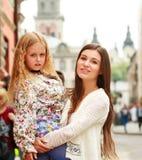 Glückliche junge Mutter, die ihre Tochter in ihren Armen in der Stadt hält Stockfotos