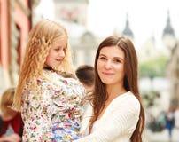 Glückliche junge Mutter, die ihre Tochter in ihren Armen in der Stadt hält Lizenzfreie Stockfotografie