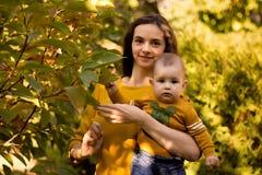 Glückliche junge Mutter, die mit Baby im Herbstpark mit gelben Ahornblättern spielt Familie, die draußen in Herbst geht Wenig Jun stockfotografie