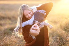 Glückliche junge Mutter, die mit Baby-Tochter draußen bei Sonnenuntergang spielt Lizenzfreie Stockbilder