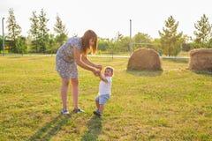 Glückliche junge Mutter, die mit ihrem kleinen Babysohn am warmen Herbst des Sonnenscheins oder am Sommertag spielt Schönes Sonne lizenzfreie stockfotografie