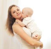 Glückliche junge Mutter mit ihrem Baby auf Händen Stockbilder