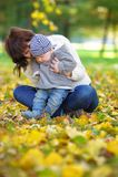 Glückliche junge Mutter mit ihrem kleinen Baby im Herbstpark Stockbilder