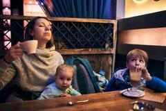 Glückliche junge Mutter mit ihren zwei sitzenden Kindern und Tee trinken stockfotografie