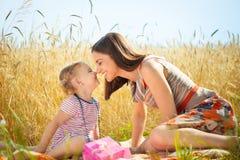 Glückliche junge Mutter mit kleiner Tochter auf Feld am Sommertag Stockbild
