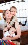 Glückliche junge Mutter mit zwei Kindern Stockbild