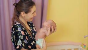 Glückliche junge Mutter rüttelt auf ihren Baby ` s Händen Das Baby gähnt mit Reisekrankheit stock video