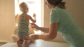Glückliche junge Mutter spielt mit ihrem schönen kleinen Jungen Babyliebkosung, Küssen, umarmend, Koketterie Kind und Frau sind z stock video footage