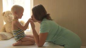 Glückliche junge Mutter spielt mit ihrem schönen kleinen Jungen Babyliebkosung, Küssen, umarmend, Koketterie Kind und Frau sind z stock video
