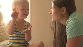 Glückliche junge Mutter spielt mit ihrem schönen kleinen Jungen Babyliebkosung, Küssen, umarmend, Koketterie Kind und Frau sind z stock footage