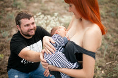 Glückliche junge Mutter stillen neugeborenes Baby, Vater sitzt nahe bei stockfoto
