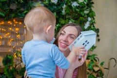 Glückliche junge Mutter und ihr Babysohn, die togerher spielt Stockfotos
