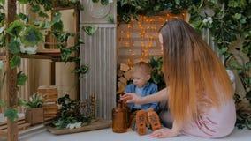 Glückliche junge Mutter und ihr Babysohn, die togerher spielt stock video
