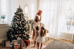 Glückliche junge Mutter und ihre bezaubernde Tochter zwei in den hübschen Kleidern lizenzfreies stockfoto
