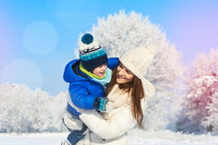 Glückliche junge Mutter und Kind, die Spaß draußen im snoy und sonnigen Tag des Winters hat Lizenzfreie Stockfotos
