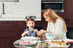 Glückliche junge Mutter und Sohn, die zusammen selbst gemachte Ostereier isst lizenzfreie stockfotografie