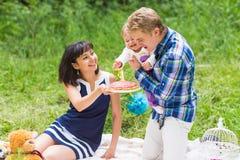 Glückliche junge Mutter und Vater mit ihrer Babytochter, die auf einer Decke in einem Park feiernd mit Geburtstagskuchen sich ent lizenzfreies stockbild