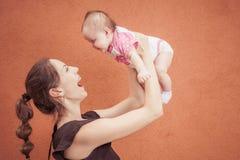 Glückliche junge Mutter werfen oben Baby auf Hintergrundorangenwand Lizenzfreie Stockfotografie