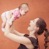 Glückliche junge Mutter werfen oben Baby auf Hintergrundorangenwand Lizenzfreie Stockbilder