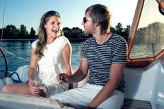 Glückliche junge Paare auf einer Yacht Lizenzfreie Stockfotografie