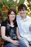 Glückliche junge Paare auf Parkbank Lizenzfreie Stockbilder